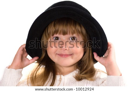 Pretty little smiling girl wearing black hat and looking at you isolated on white