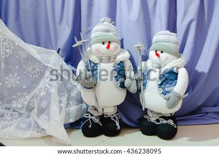 Pretty little snowmen-skiers stand on the floor - stock photo