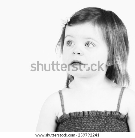 Pretty little toddler in studio with thoughtful expression - stock photo