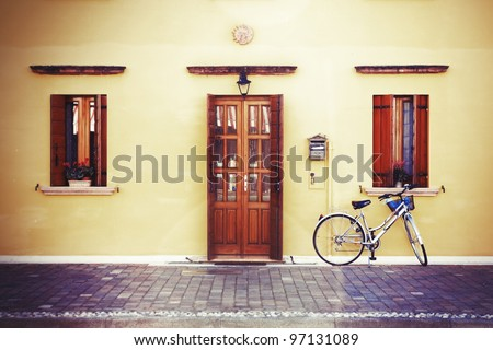 Pretty lonely bike by classic style house entrance (yellow walls, wooden door and windows decorated with flowerpots), vintage aged blurry photo effect added - stock photo