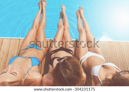 Pretty long legs. Top view of three beautiful ladies sitting at poolside stretching out their nice legs. - stock photo