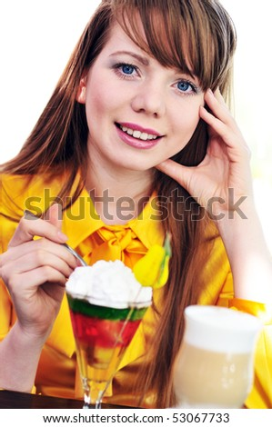 pretty longhaired blue-eyed girl enjoying cream and dessert in cafe - stock photo