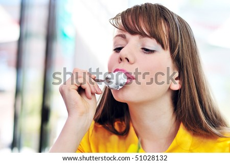 pretty longhaired girl enjoying cream in outdoors cafe - stock photo
