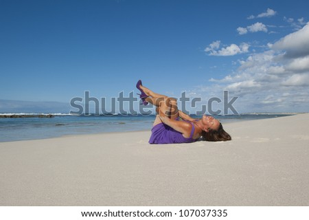Pretty looking mature woman in sexy purple dress and high heel shoes at the beach, with ocean and blue sky as background and copy space. - stock photo