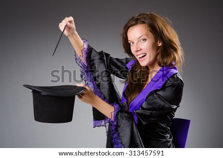 Pretty magician girl holding stick against gray - stock photo
