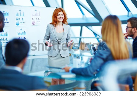 Pretty manager explaining her point of view to colleagues at meeting - stock photo
