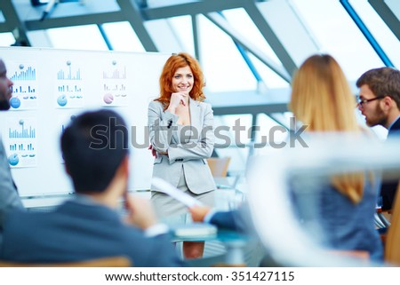 Pretty manager listening to colleagues while standing by whiteboard - stock photo