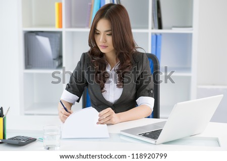 Pretty manager signing documents in her office