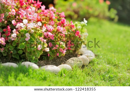 Pretty manicured flower garden with red flowers - stock photo