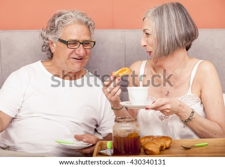 pretty mature couple have fun in the bed while eating breakfast