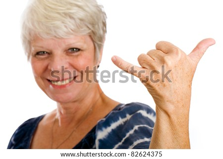 Pretty, mature, gray haired woman giving the Hawaiian sign for hang loose. - stock photo