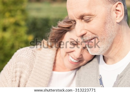 Pretty mature husband and wife are standing and embracing in park. They are smiling - stock photo