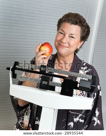 Pretty mature, woman on a medical scale with an apple illustrating sensible, healthy dieting.