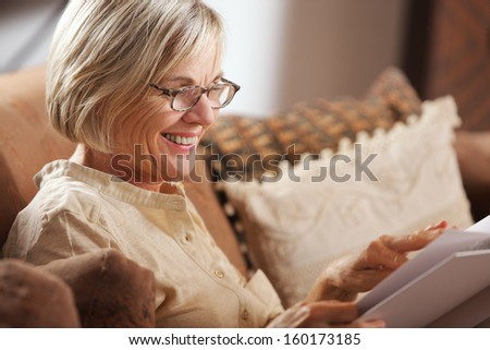 Pretty mature woman passing her time by reading a book  - stock photo