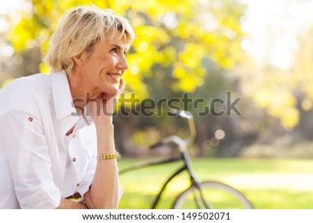 pretty mature woman relaxing outdoors - stock photo