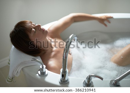 Pretty mature woman with her eyes closed in a bathtub - stock photo