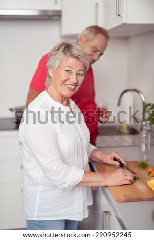 Pretty Matured Housewife Slicing Recipe Ingredients at the Kitchen While her Husband is Watching Over her. - stock photo