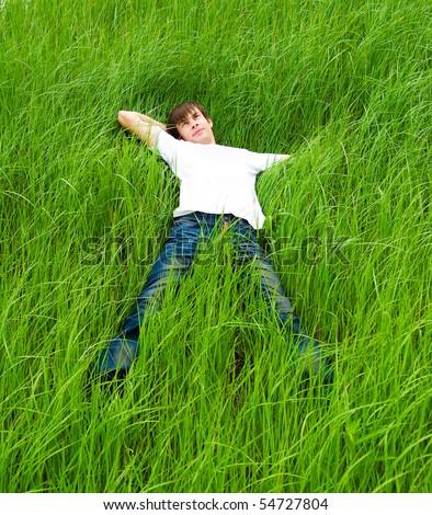 Pretty men lie on the green grass - stock photo