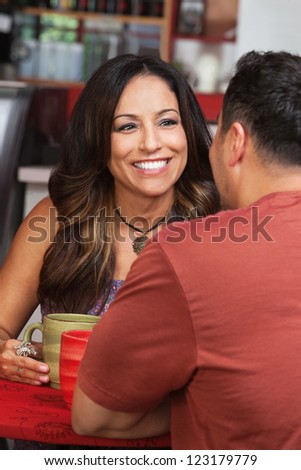 Pretty Mexican woman with male friend in cafe - stock photo