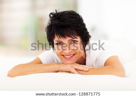 pretty mid aged woman lying on bed at home - stock photo