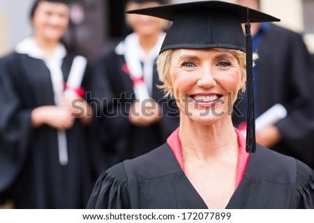 pretty middle aged university professor at students graduation ceremony - stock photo