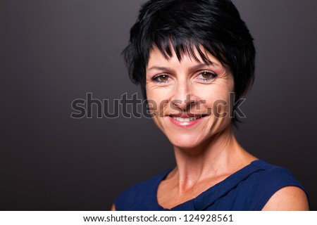 pretty middle aged woman closeup portrait on black - stock photo