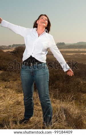 Pretty middle aged woman enjoying outdoors. Clear sunny spring day with blue sky. - stock photo