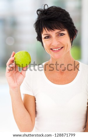 pretty middle aged woman holding a green apple