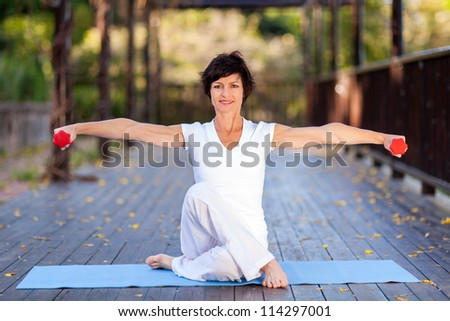 pretty middle aged woman workout with dumbbells - stock photo