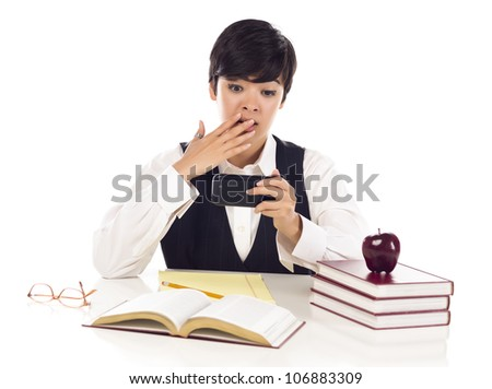 Pretty Mixed Race Female Student at Desk with Books Has Shocked Look from Cell Phone Message Isolated on a White Background. - stock photo