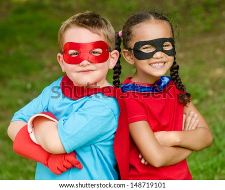 Pretty mixed race girl and Caucasian boy pretending to be superhero