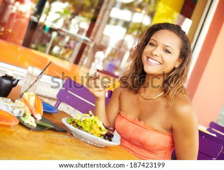 Pretty Mixed Race Woman Enjoying A Meal At A Restaurant. African American female enjoying japanese cuisine at a fancy restaurant, using chopstick and really happy. - stock photo