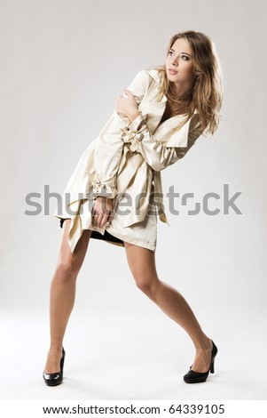 Pretty model in beige fashionable raincoat posing against gray background - stock photo