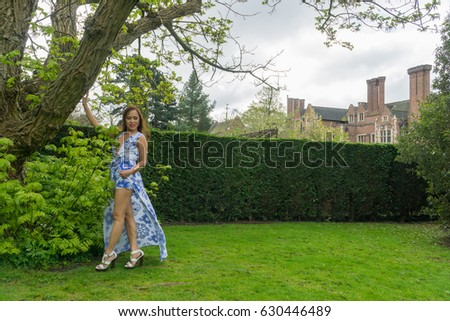 Pretty model in blue dress with long hair Filipino woman, in a park