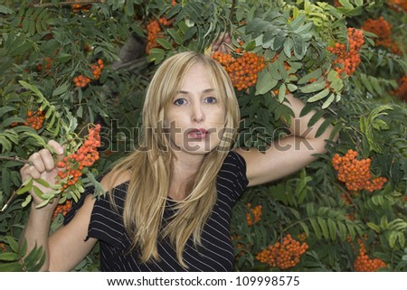Pretty model posing in outdoor admiring ashberry tree - stock photo