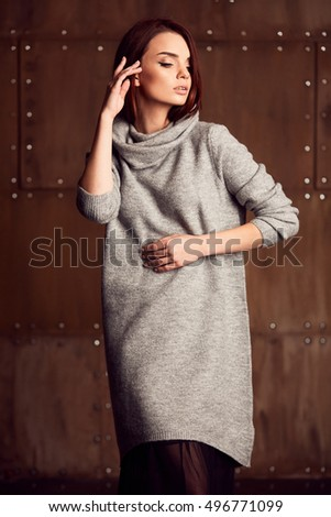Pretty model posing in studio in grey dress