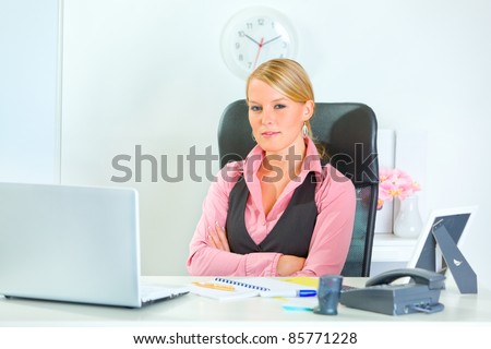 Pretty modern business woman sitting at office desk with crossed arms - stock photo