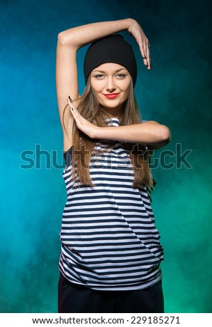 Pretty modern hip-hop style girl is dancing isolated on a colored background. - stock photo