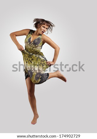 pretty modern slim hip-hop style woman jumping dancing on a colour background - stock photo