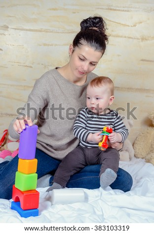 Pretty Mom and her Cute Baby Boy Playing with Colored Plastic Blocks at Home Together. - stock photo