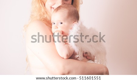 Pretty mom embracing her beautiful baby with wings of an angel isolated on white