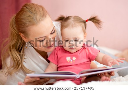 pretty mom reading a book to baby daughter at home - stock photo
