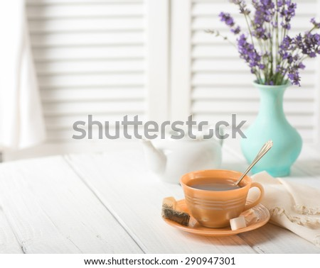 Pretty Morning Tea in Vintage Cup with Cyan Vase and Lavender Flower bouquet with pot against Rustic White Wood Board Background with room or space for copy, text, words.  High key side light. - stock photo