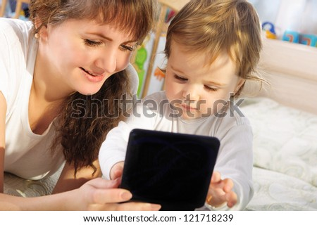 Pretty mother and baby son playing with digital tablet