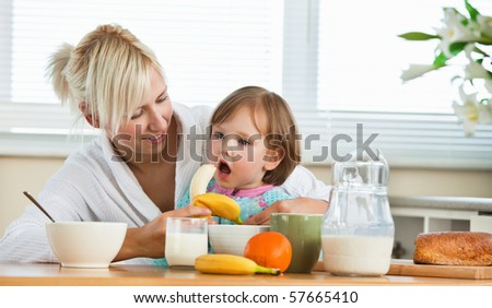 Pretty mother and daughter having breakfast in kitchen