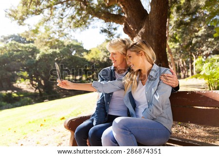 pretty mother and daughter taking self portrait with smart phone - stock photo