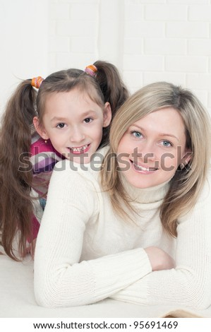 Pretty mother and her cute daughter lying on the floor, smiling and looking at camera