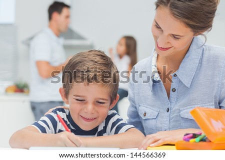 Pretty mother drawing with her son while father is discussing with his daughter on the background