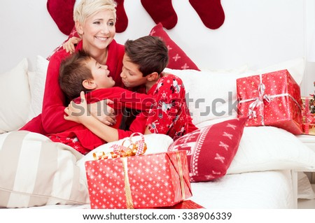 Pretty mother having fun with sons. Christmas time. Happiness content. Photo at home, bedroom. Christmas decorations.