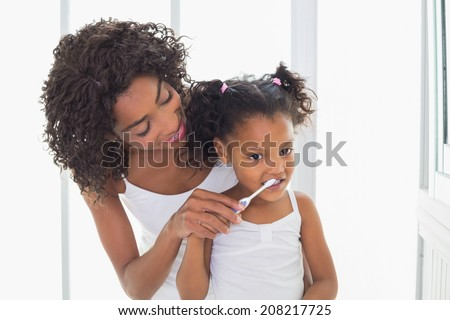 Pretty mother helping her daughter brush her teeth at home in the bathroom - stock photo